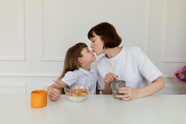 ミディアムショットの母と少女が一緒に座っている