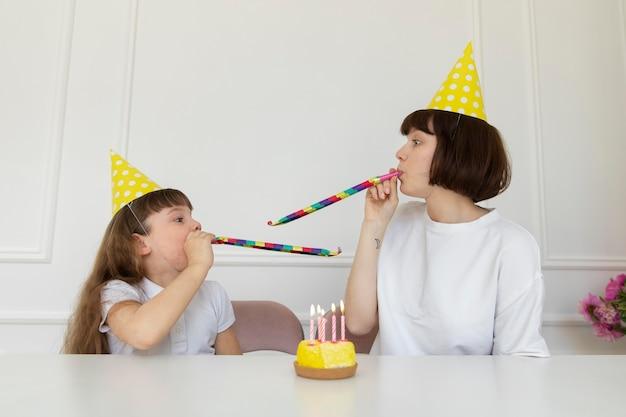 ミディアムショットの母とパーティーの角を持つ少女