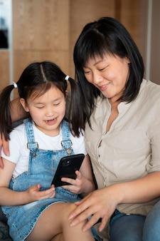 ミディアムショットの母と電話を持つ少女