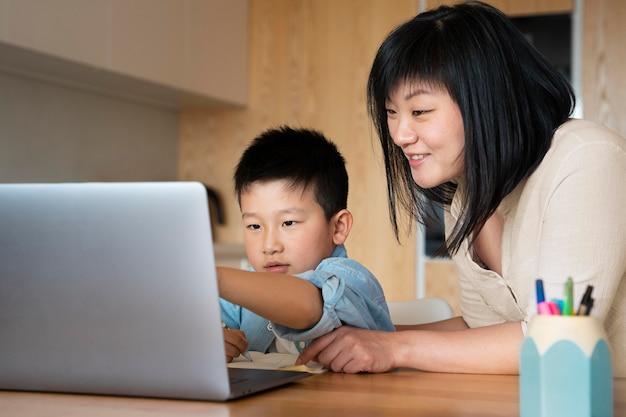 ミディアム ショットの母とラップトップを持つ子供