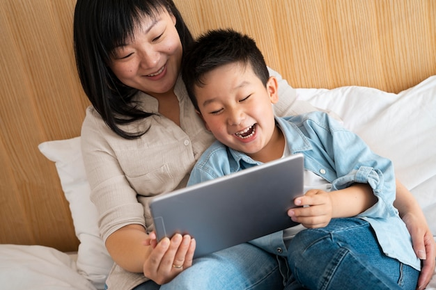 Medium shot mother and boy with tablet