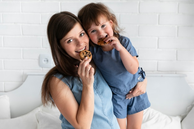 Medium shot mother and daughter eating chocolate cookies