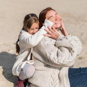 Medium shot mother and girl at beach
