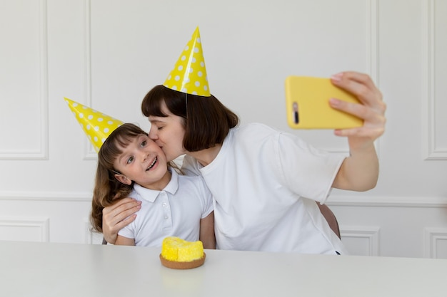 Medium shot mother and girl taking selfies with phone