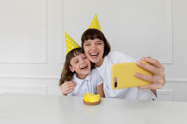 Medium shot mother and girl taking selfies