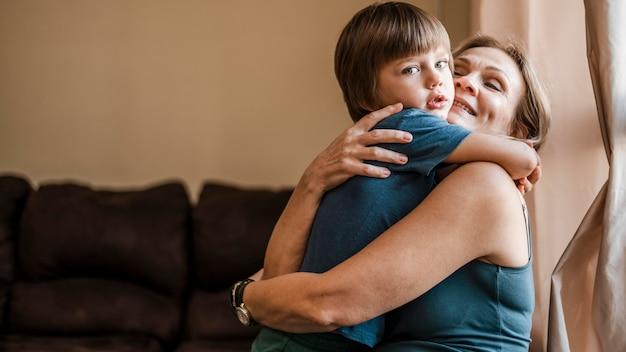 Средний выстрел мать держит мальчика
