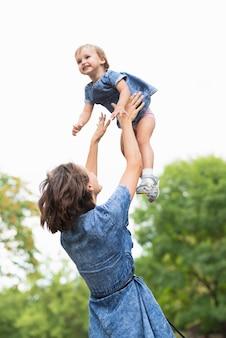 Medium shot of mother holding her daughter