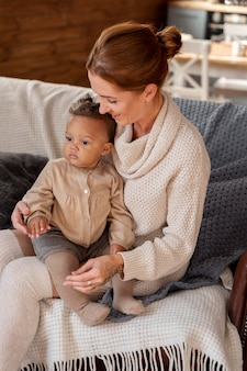 Medium shot mother holding kid on couch