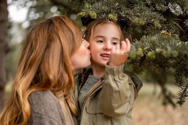 Medium shot mother kissing daughter