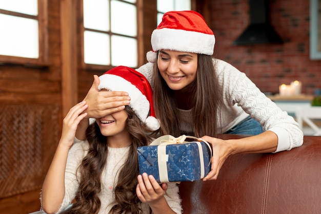 Medium shot mother surprising daughter with gift