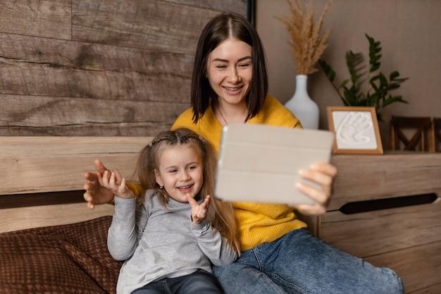 子供とラップトップを持つミディアムショットの母親