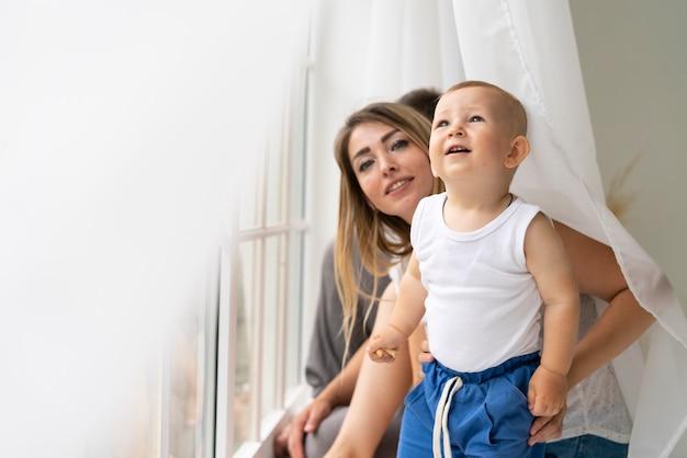 窓の近くの息子とミディアムショットの母