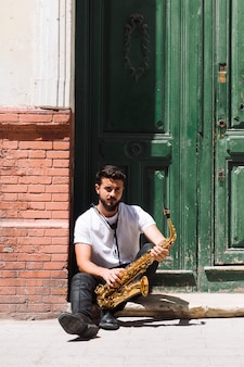 Medium shot musician sitting and posing with sax