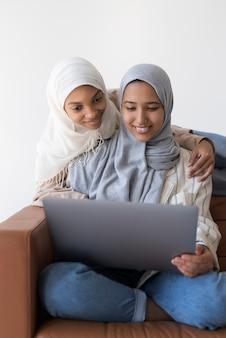 Средний снимок мусульманских женщин с ноутбуком