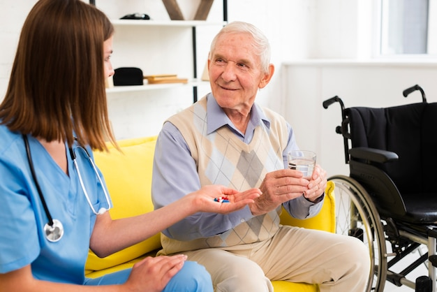 Medium shot nurse giving an old man his pills