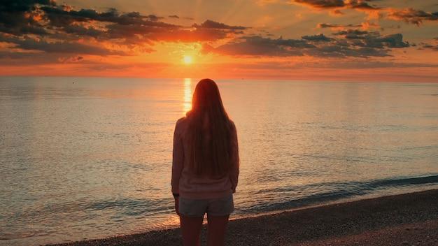 手を上げて海岸の女性の日の出を賞賛するミディアムショット背面図