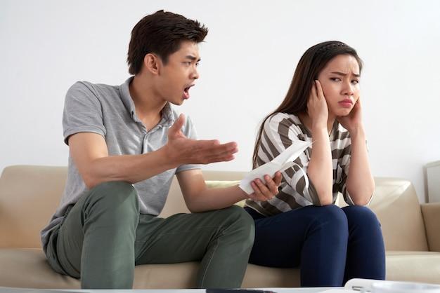 한 장의 종이를 들고 그의 아내에 외치는 아시아 남자의 중간 샷