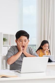 Средний снимок азиатских учеников в классе, работающих на ноутбуках, мальчик впереди с удивленным выражением на лице