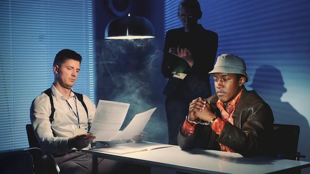 尋問室で白人刑事と面接している手錠をかけられた黒人囚人のミディアムショット