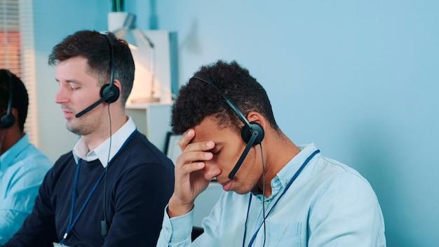 Средний снимок скучающего и недовольного черного агента колл-центра, разговаривающего с клиентом по телефону, он ...