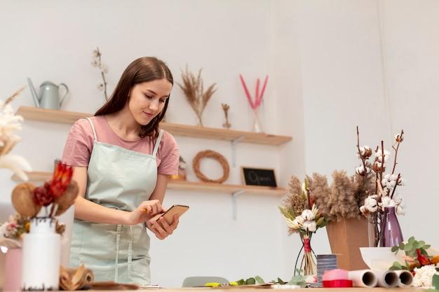 Средний снимок деловой женщины, используя ее мобильный телефон