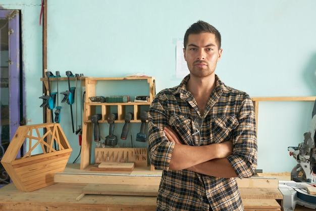 自信を持って立っている腕のミディアムショットは、大工仕事の店で折り畳まれて