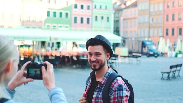 역사적인 시장 광장 맨 포에서 사진 카메라로 사진을 찍는 관광객 커플의 중간 샷...