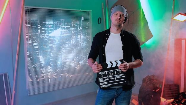 カメラに微笑んで、映画のカチンコでアクションを与える映画プロデューサーアシスタントのミディアムショット
