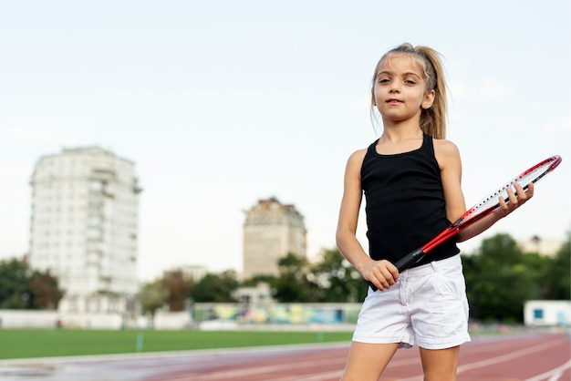 赤いテニスラケットを持つ少女のミディアムショット