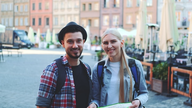Средний снимок счастливой молодой пары туристов, проверяющих карту, а затем улыбающихся в камеру. они стоят на большой рыночной площади старого европейского города.