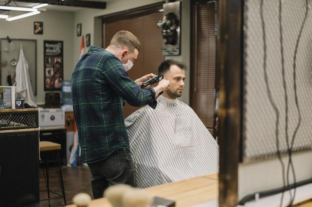 散髪を受ける男性のミディアムショット