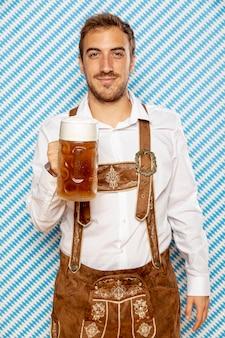 맥주 파인트를 들고 남자의 중간 샷 무료 사진