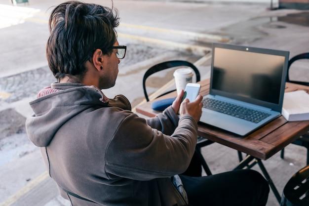 바에 앉아 노트북 작업을 하는 동안 메시지에 답하는 남자의 중간 샷. 온라인 작업 개념입니다.