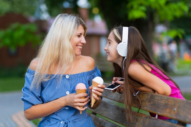 Средний снимок мамы и дочки с мороженым