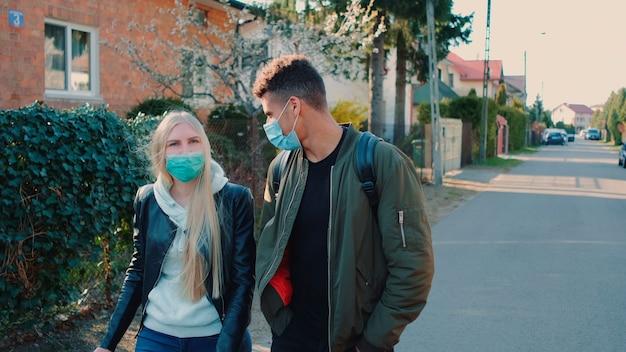 Средний снимок многонационального мужчины и женщины в медицинских масках, идущих по улице в жилом массиве. они вместе проводят свободное время.