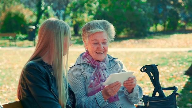 彼女のかわいい孫娘に彼らが美しさのベンチに座っている手紙を見せている老婆のミディアムショット...
