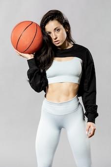 Средний снимок спортивной женщины с баскетбольным мячом