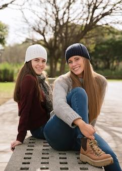 Средний снимок двух улыбающихся женщин, сидящих на скамейке