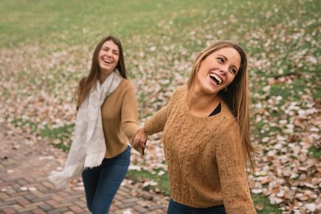 公園で手を繋いでいる2人の女性のミディアムショット