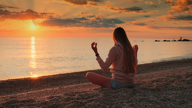 日没の沈黙とリラクゼーションの概念の前に海の上で瞑想をしている女性のミディアムショット