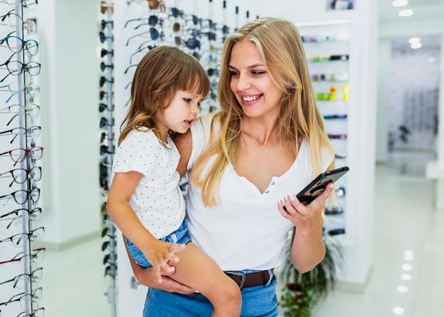 Средний снимок женщины, держащей ребенка и телефон
