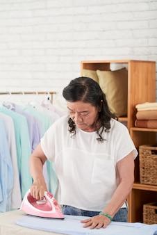 Средний снимок женщины, гладящей одежду дома