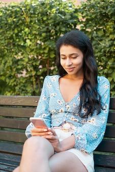 彼女の携帯電話を見ている女性のミディアムショット