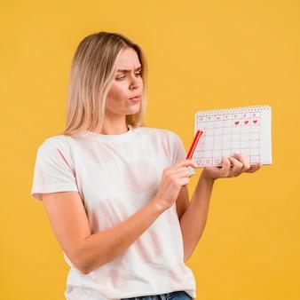 Средний снимок женщины, показывающей календарь периода