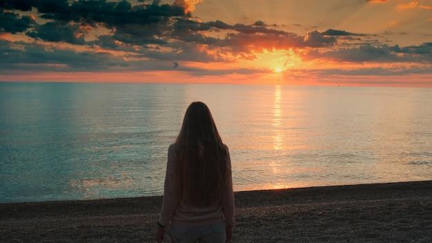 長い髪の女性が海に向かって歩いて手を上げてサンセットバを見ているミディアムショット...