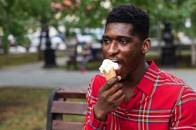 公園でアイスクリームを食べる赤いシャツの若い大人のミディアムショット