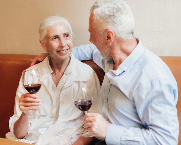 Medium shot old couple drinking wine