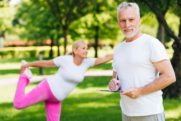 Medium shot old couple exercising outdoors