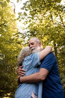 Medium shot old couple hugging