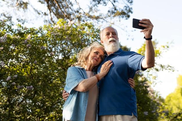 ミディアムショットの老夫婦が自分撮りをしている